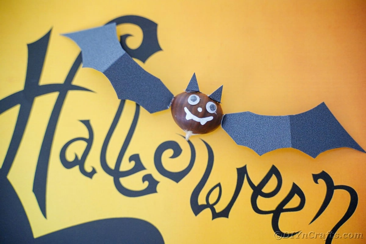 Yellow paper with black word Halloween holding bat decoration