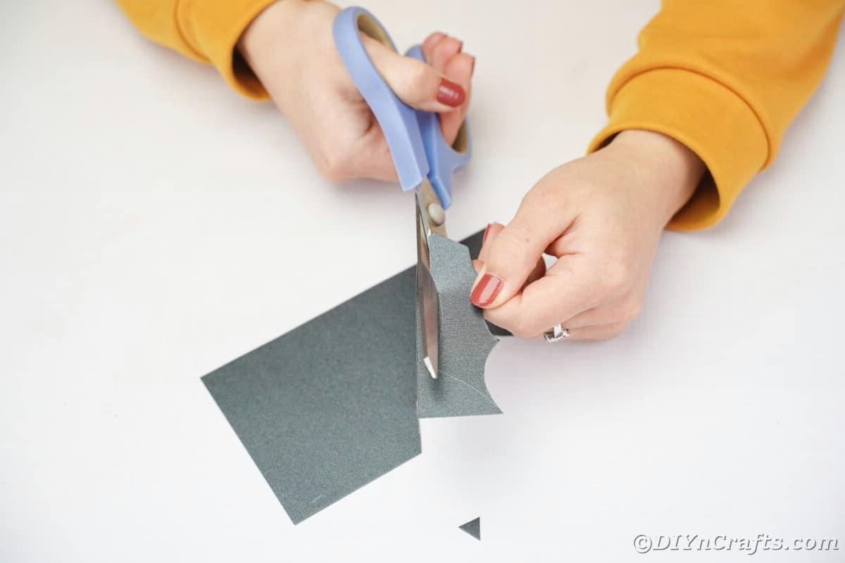 Cutting bat wings out of black paper using blue scissors