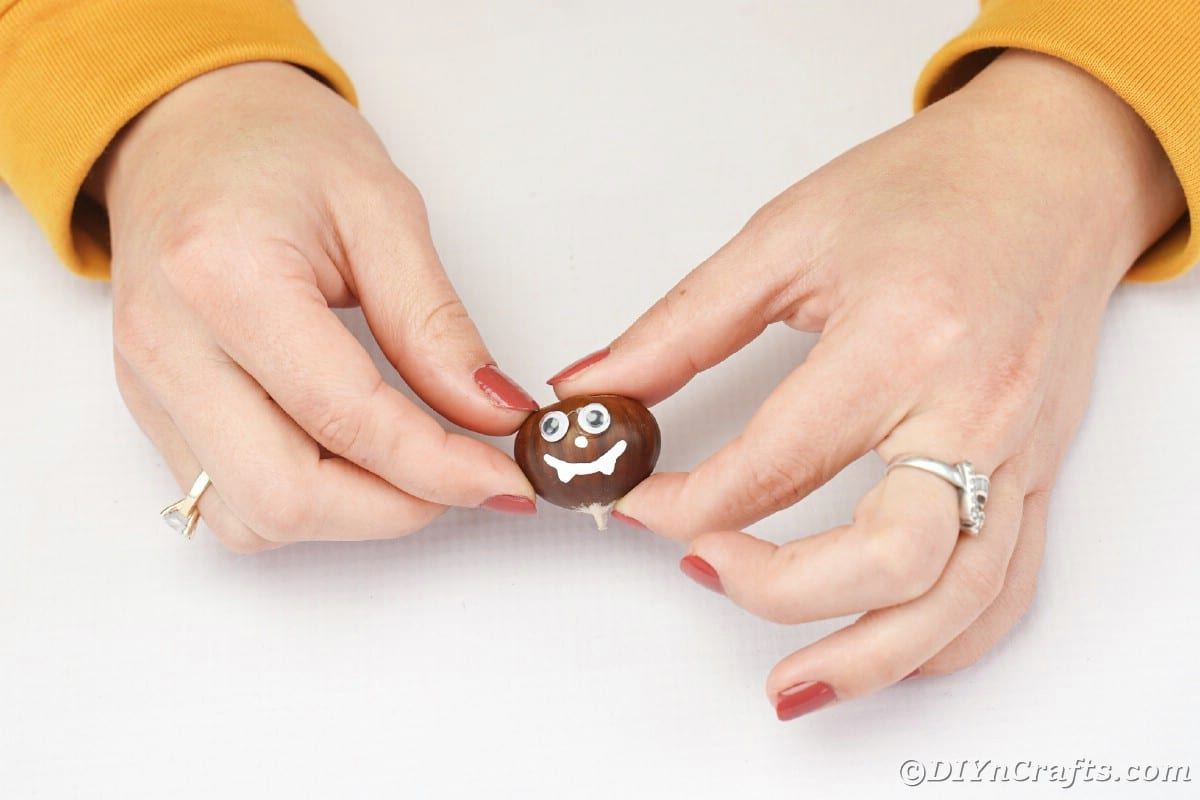 Woman holding chestnut with face painted on it