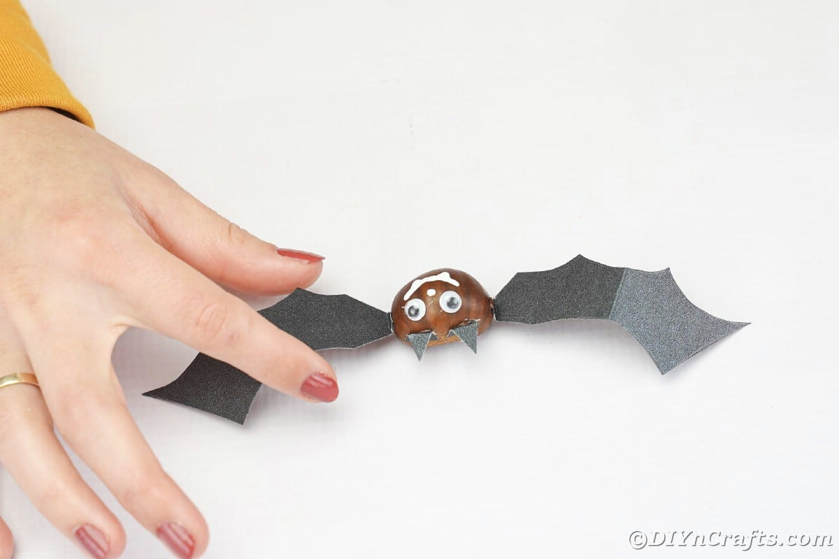 Hand holding paper wing against chestnut bat face