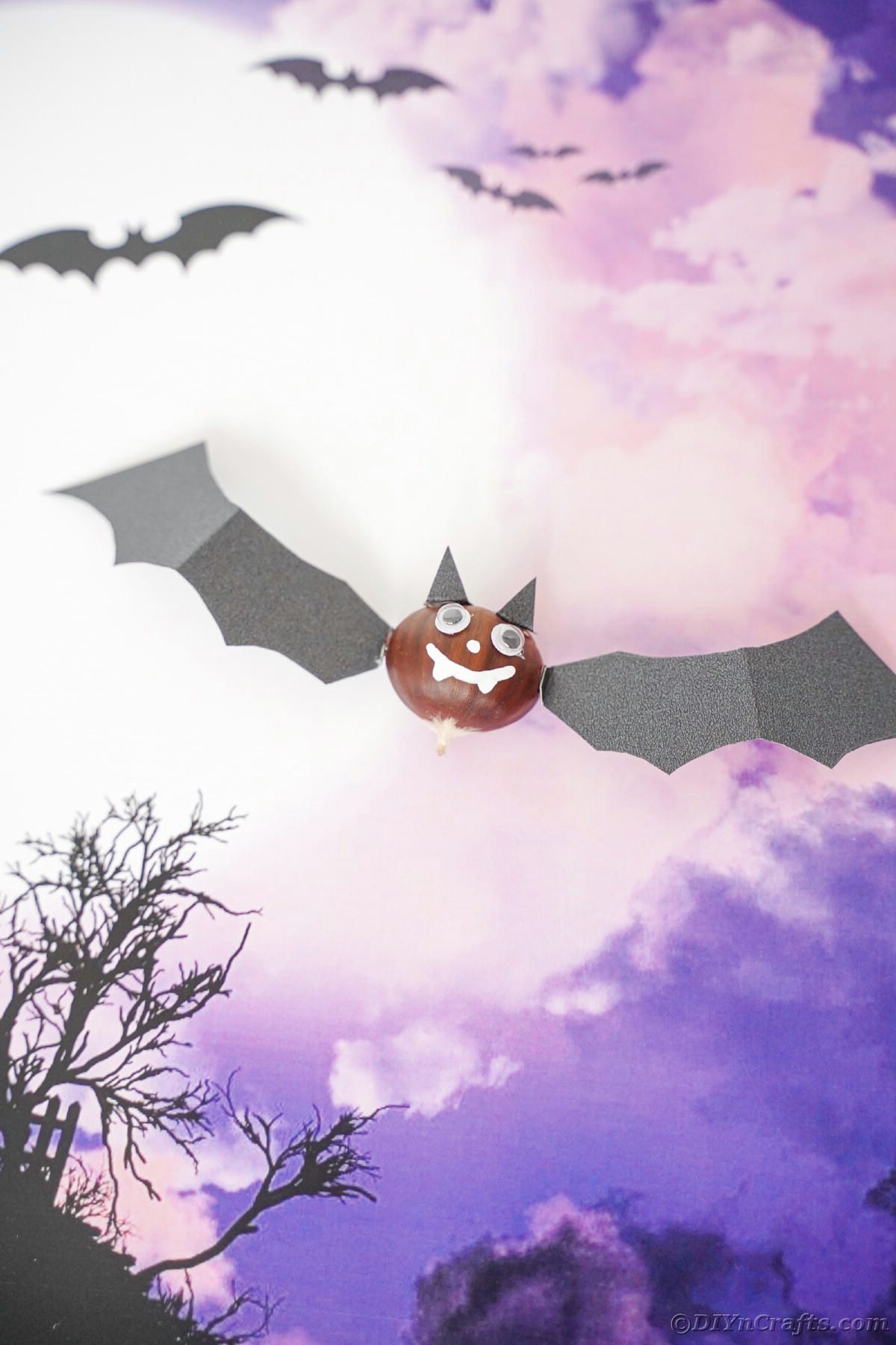 Bat decoration laying on top of purple scrapbook paper