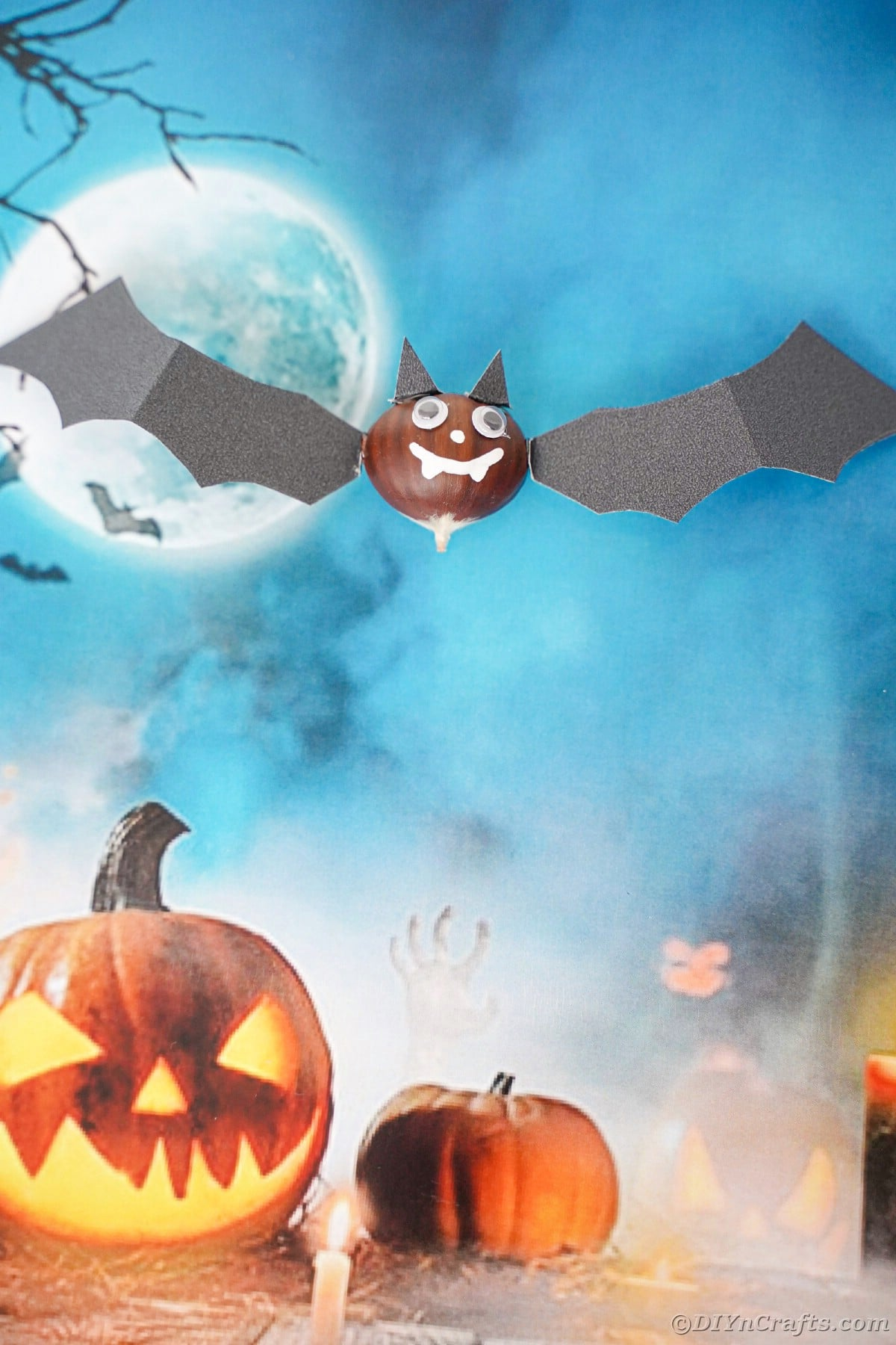 Crafted bat on top of blue scrapbook Halloween paper background