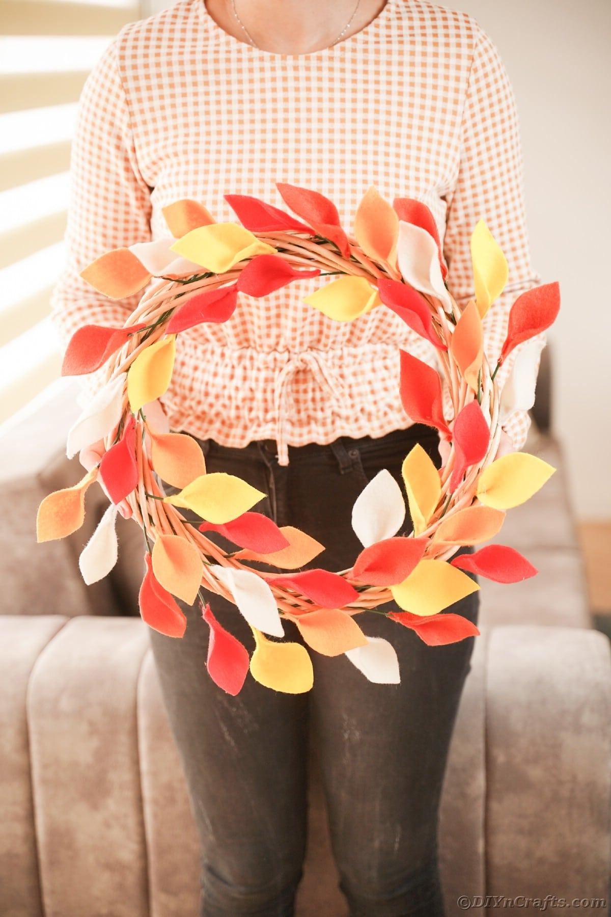 Mulher segurando uma coroa de folhas coloridas