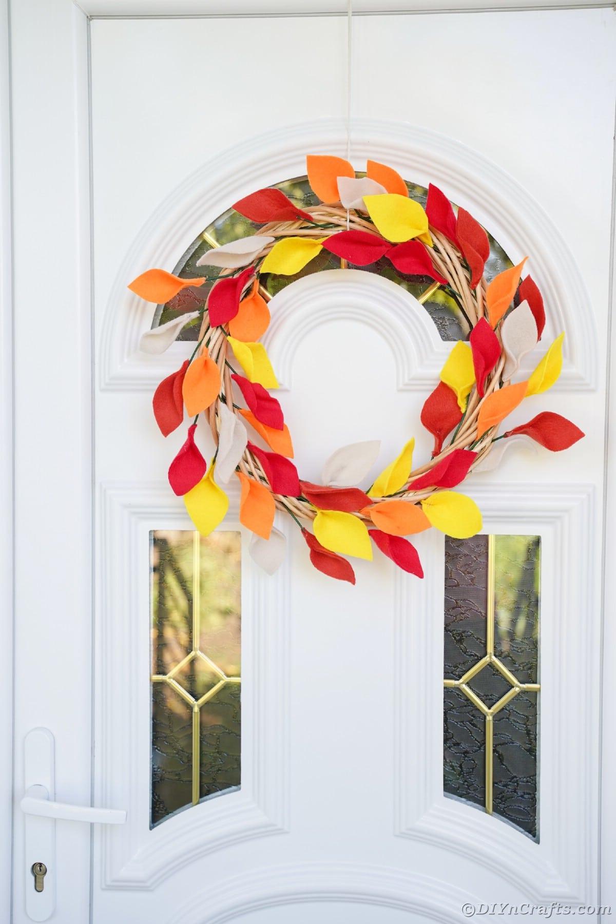 Coroa de outono pendurada na porta branca