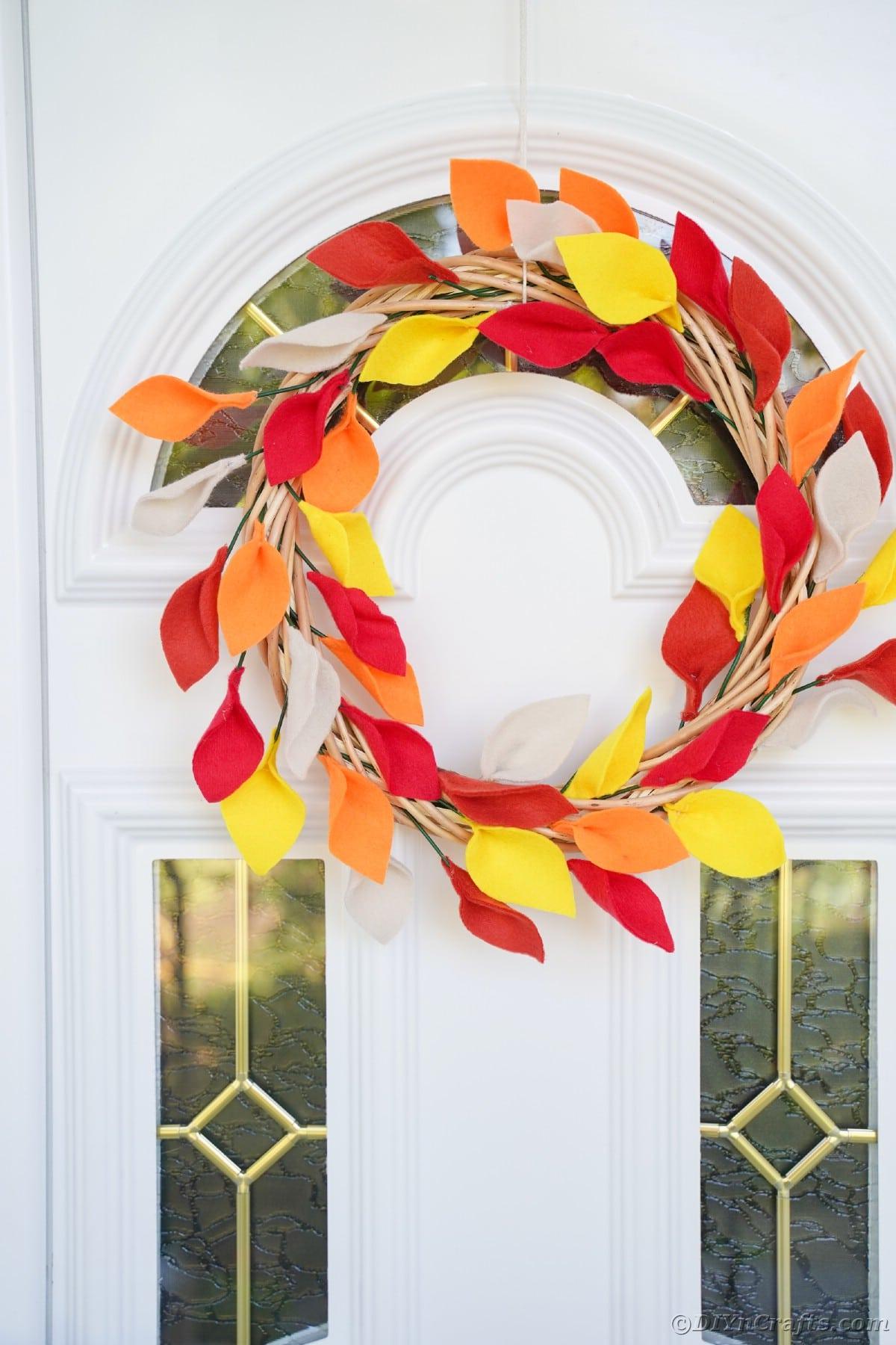 Coroa de outono pendurada na porta branca com detalhes em vidro
