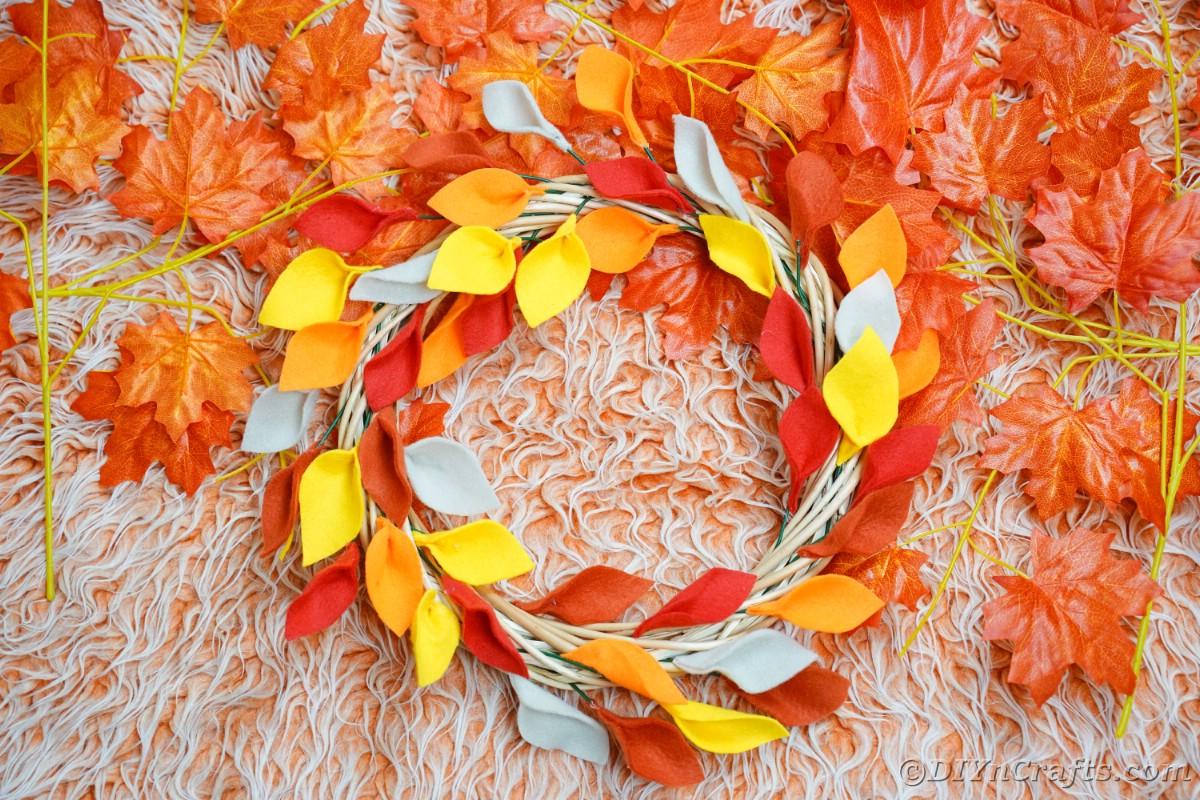 Coroa de folhas de outono no tapete laranja