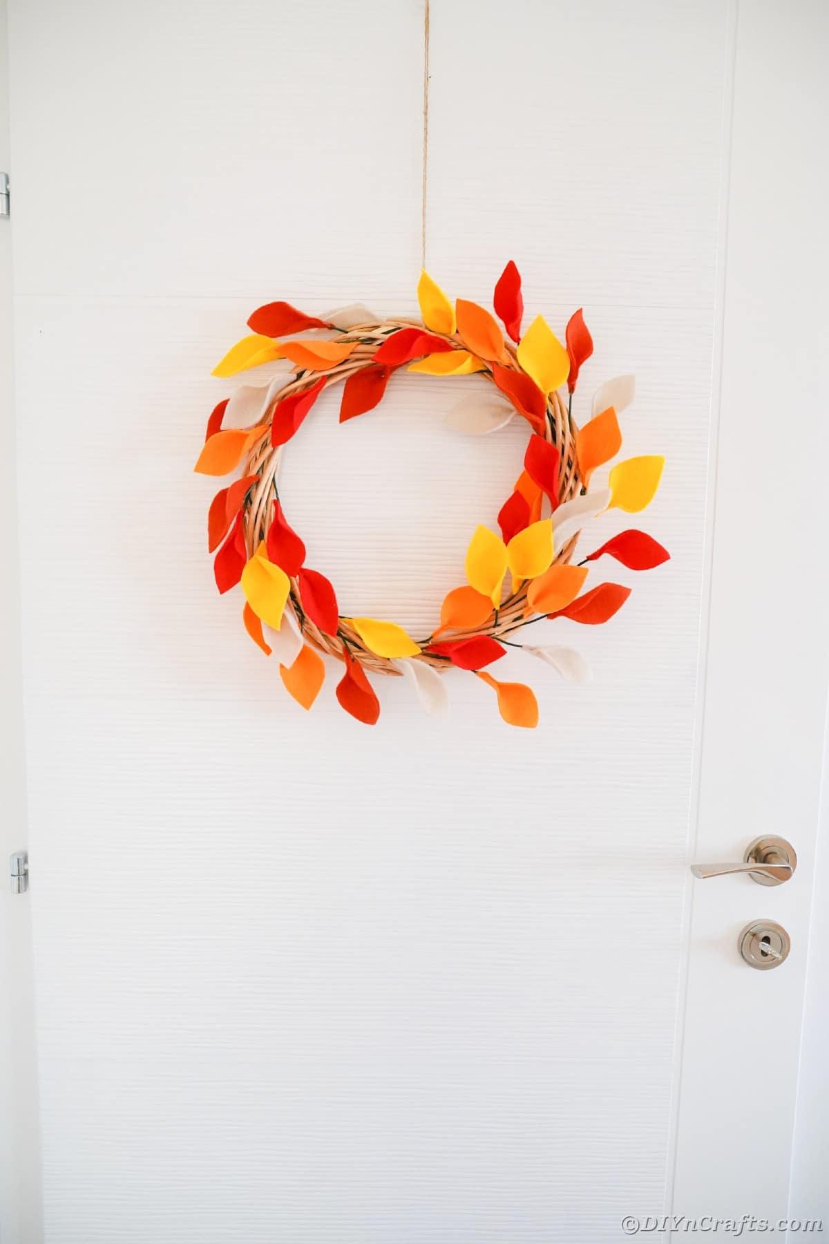 Guirlanda de folhas pendurada na porta branca