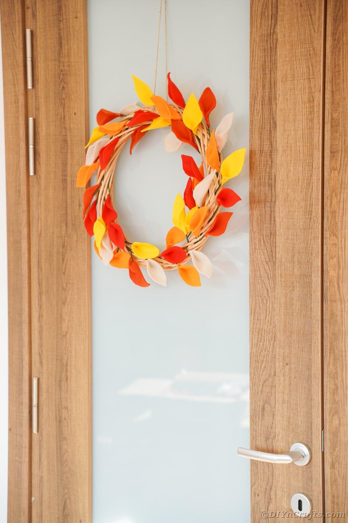 Porta de madeira e vidro com coroa de folhas