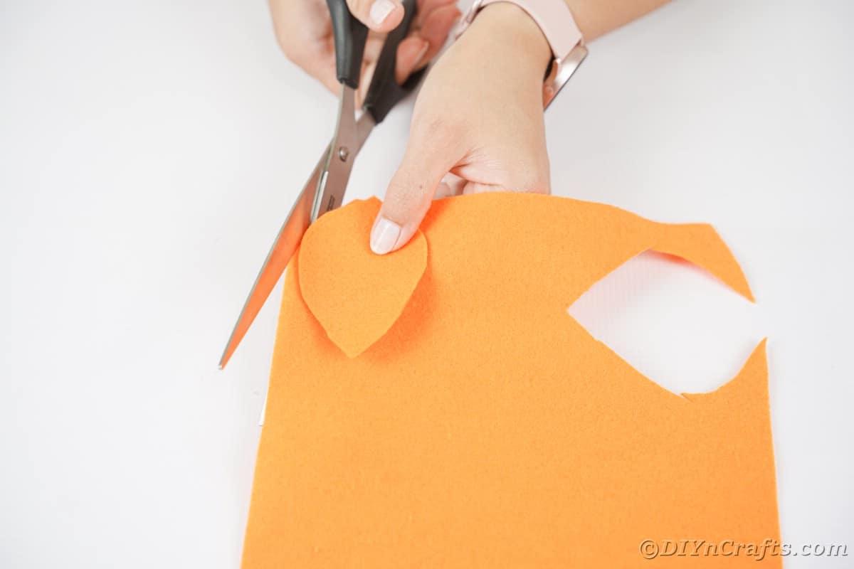 Mão cortando uma folha de feltro laranja