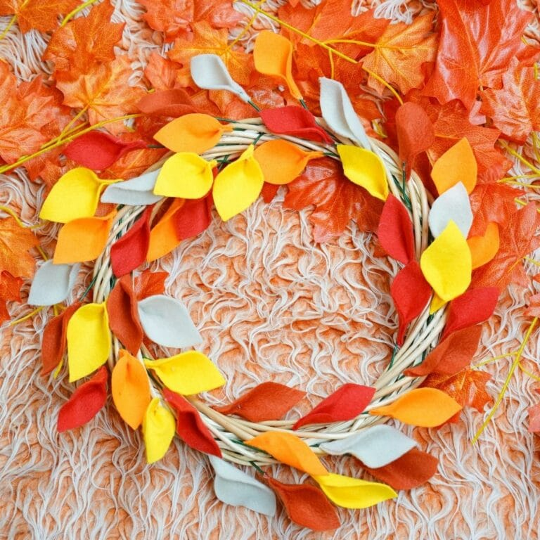 Fall leaf wreath on orange rug surrounded by fake leaves
