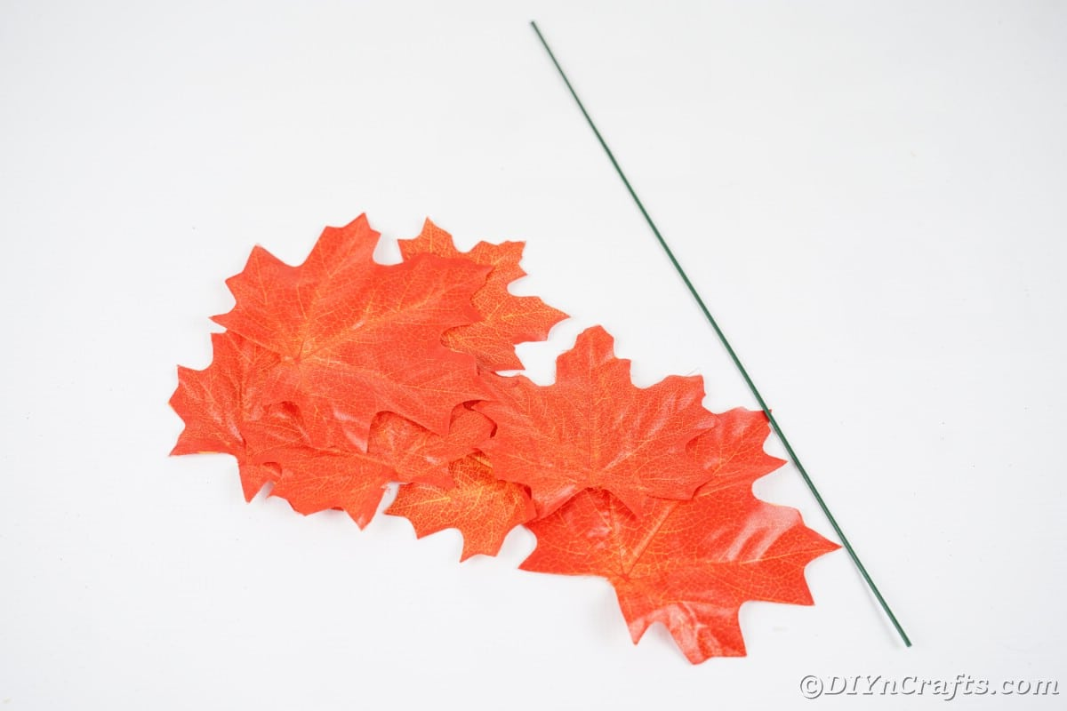 Fake orange leaves and floral wire on white table