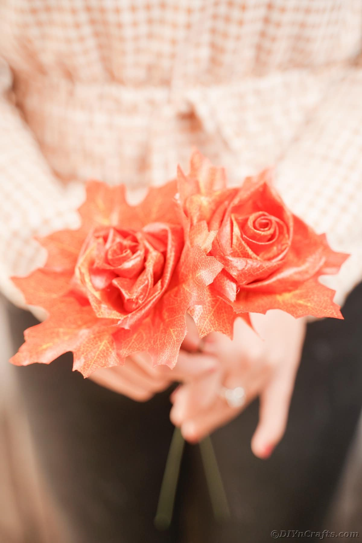 Woman in black pants holding two fake roses