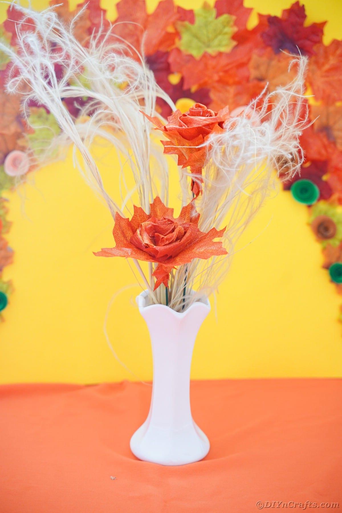 Orange leaf rose and white branches in white vase