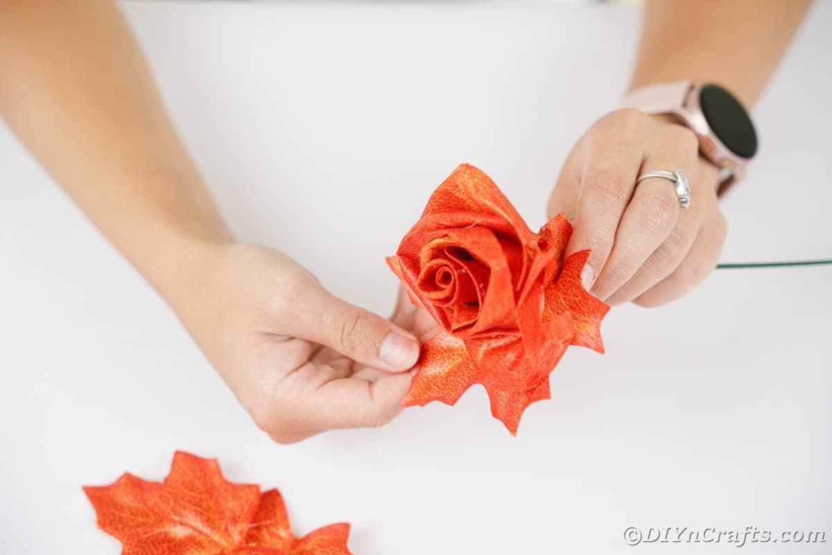 Hand touching leaf on fake rose