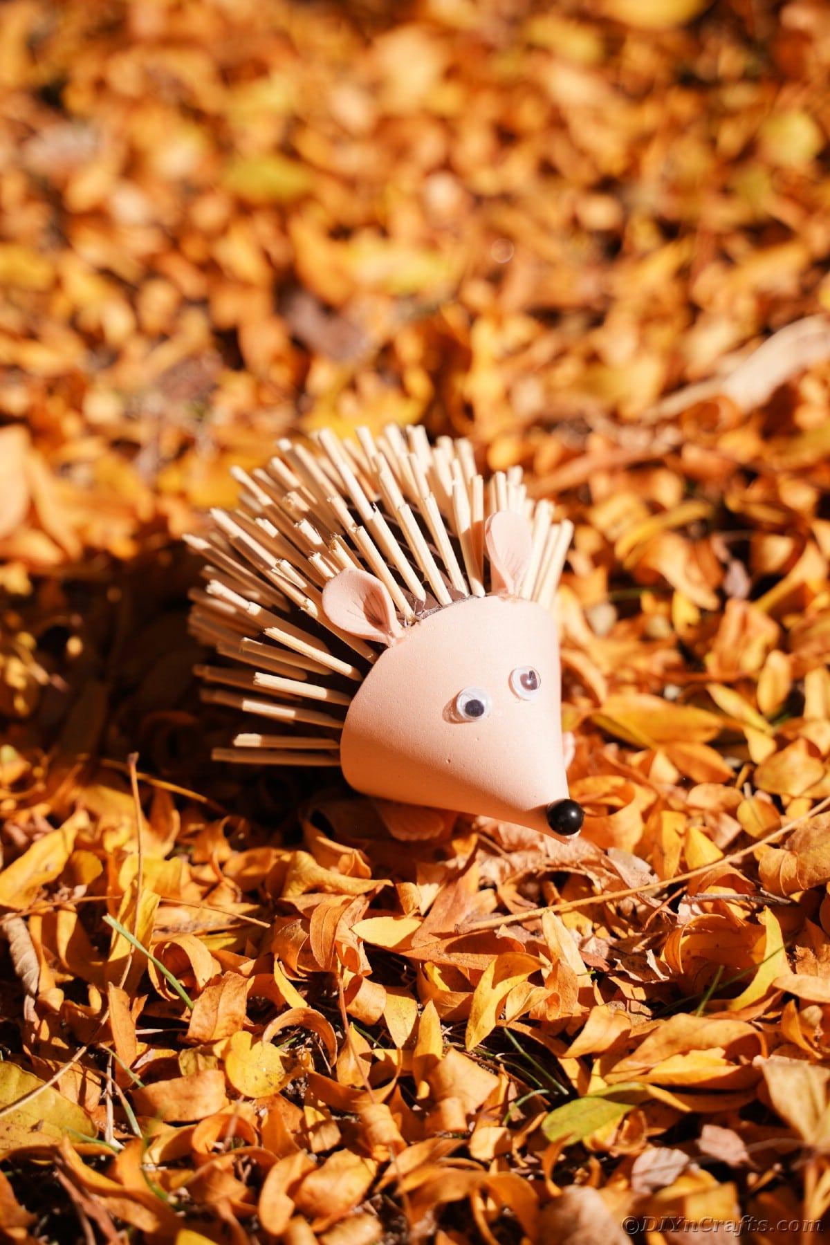 Pile of orange leaves with mini foam hedgehog on top