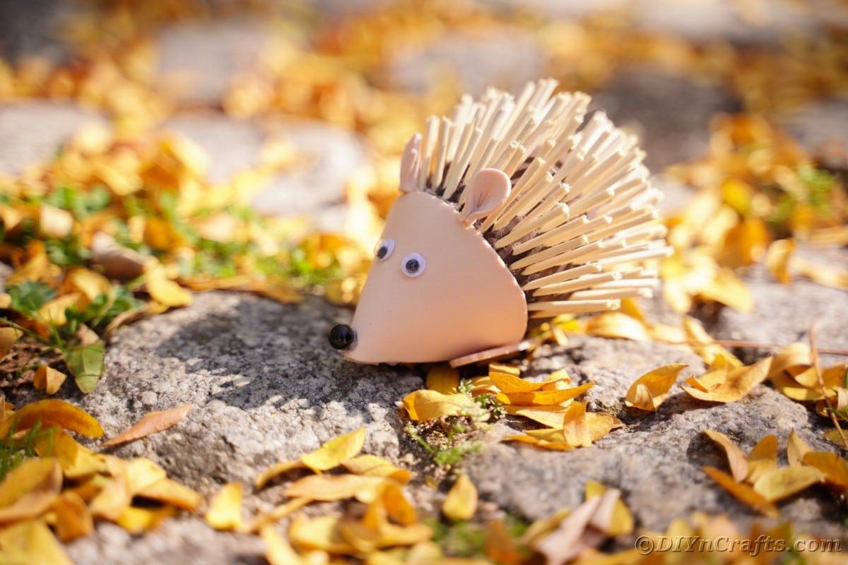 Toy hedgehog sitting on rocks