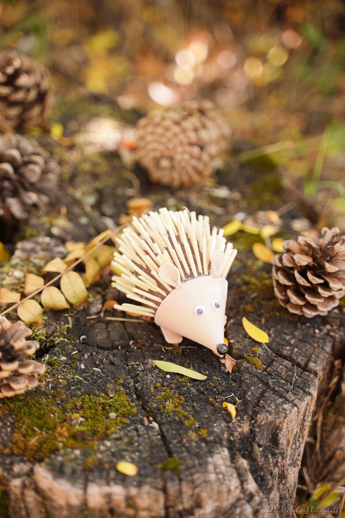 Foam hedgehog sitting on stump with pinecones