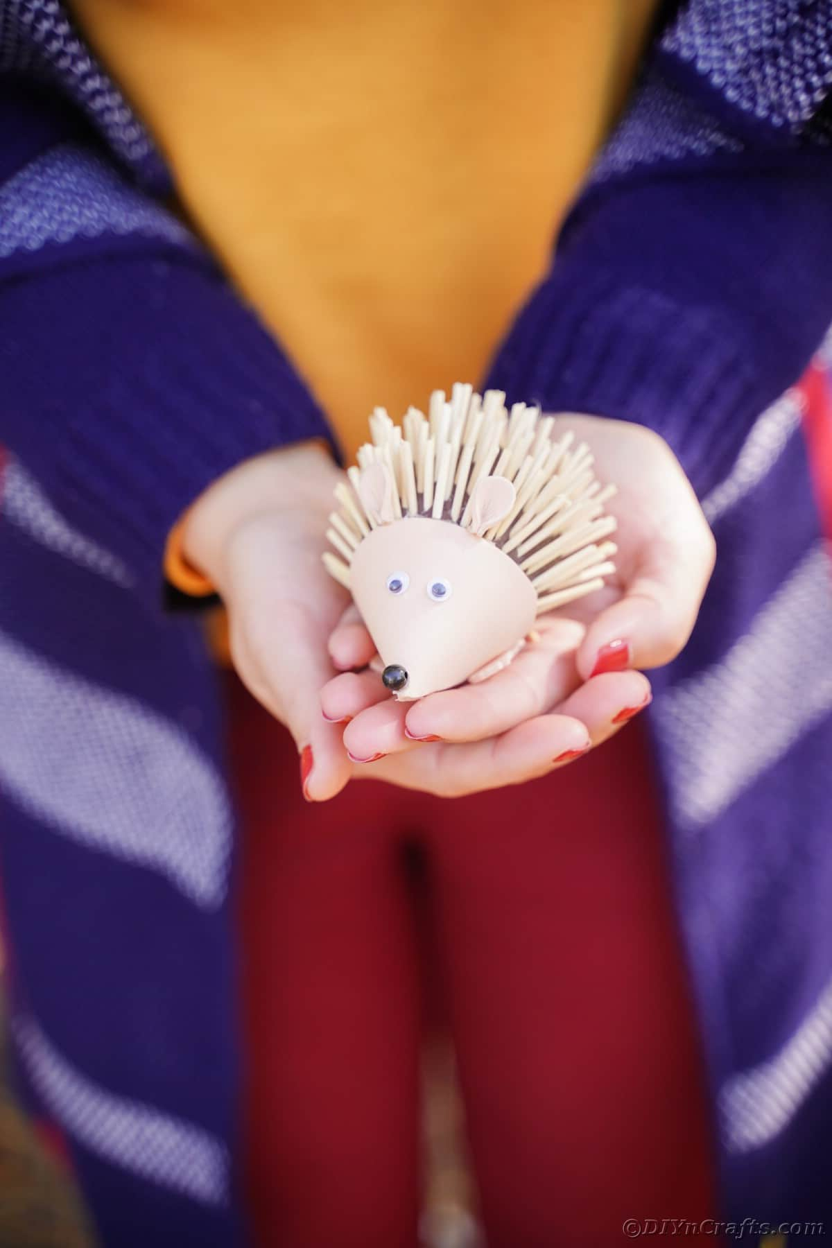 Woman in blue jacket holding hedgehog toy in hands