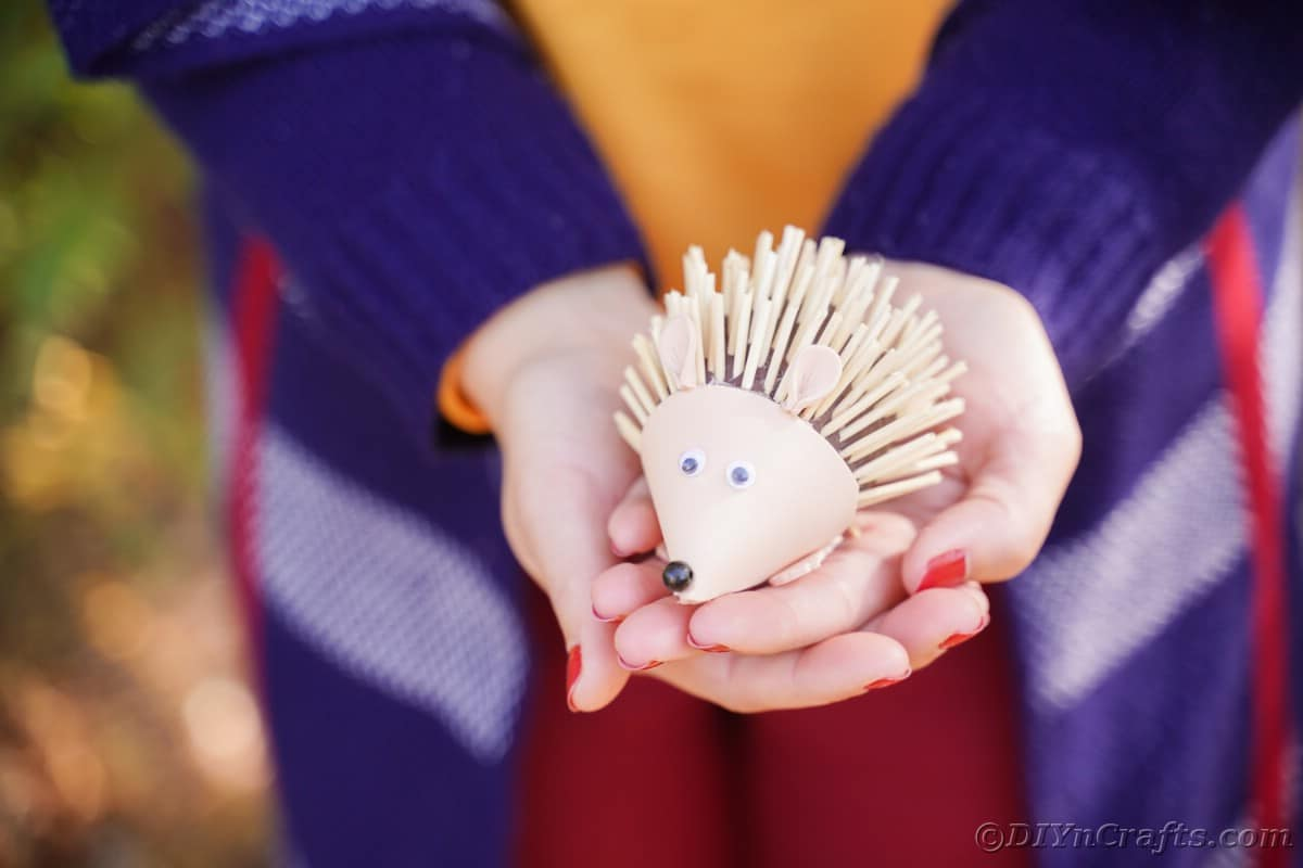 Foam hedgehog in hands of woman in orange shirt