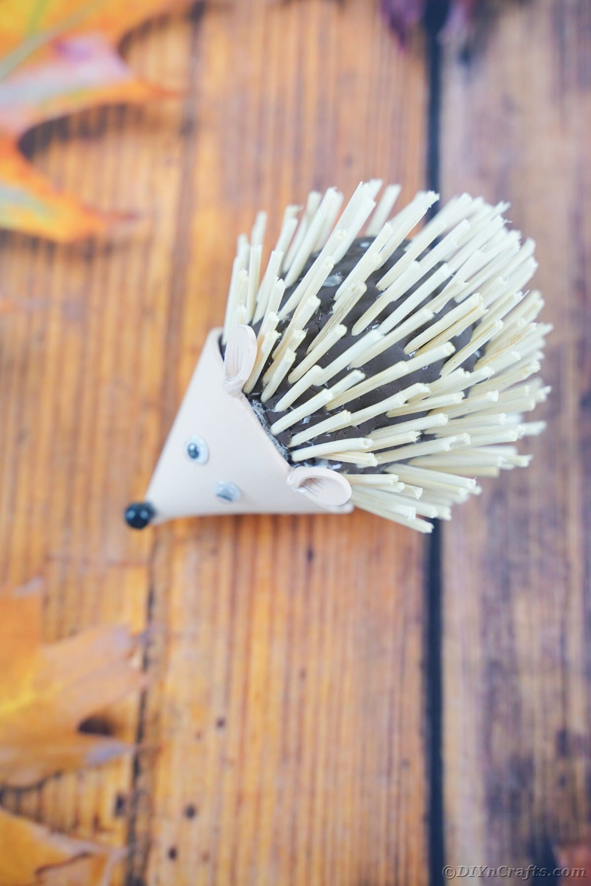 Wood slat table with fall leaves and toy hedgehog on top
