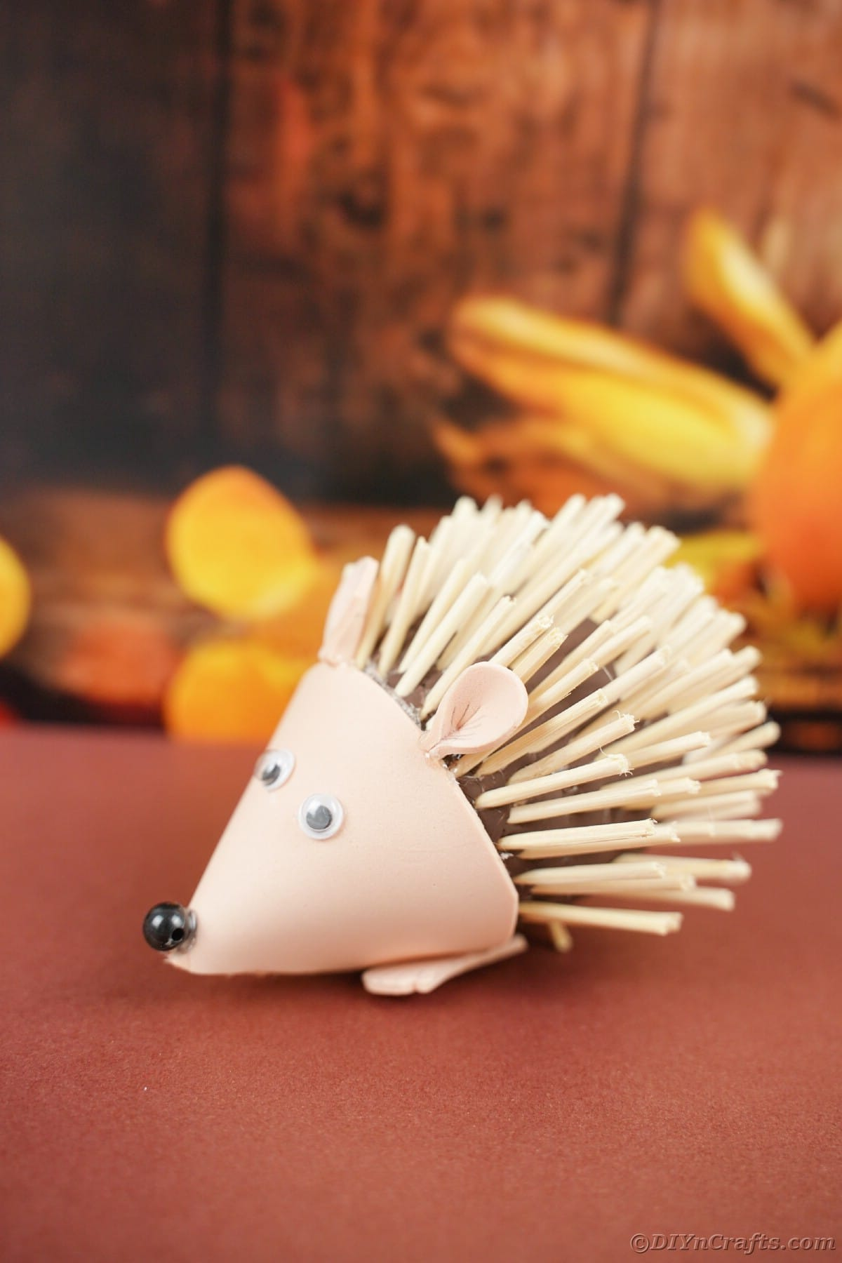 Mini hedgehog toy on brown table in front of fall scene