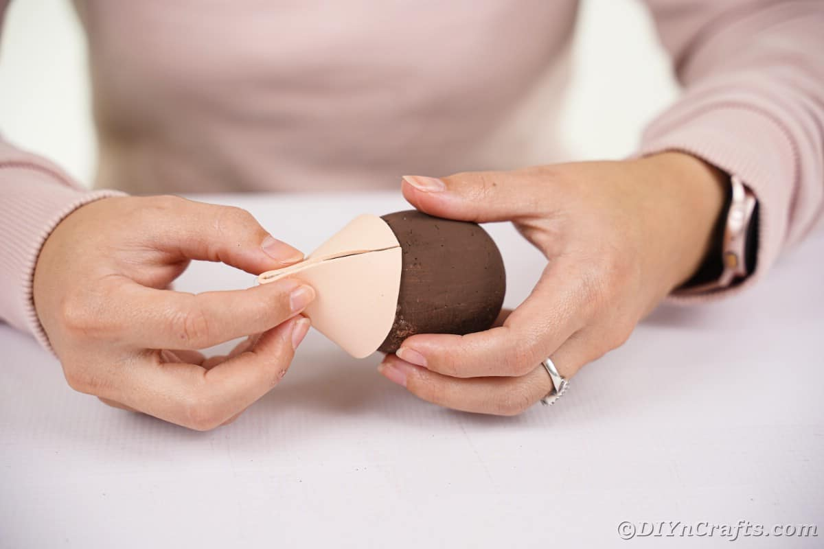 Gluing the tan paper to the brown egg