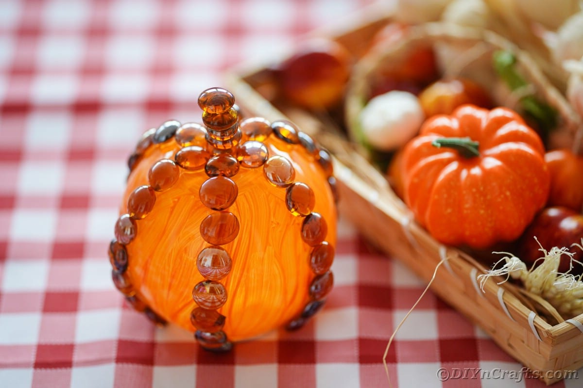 Fake pumpkin next to wood tray on checked tablecloth