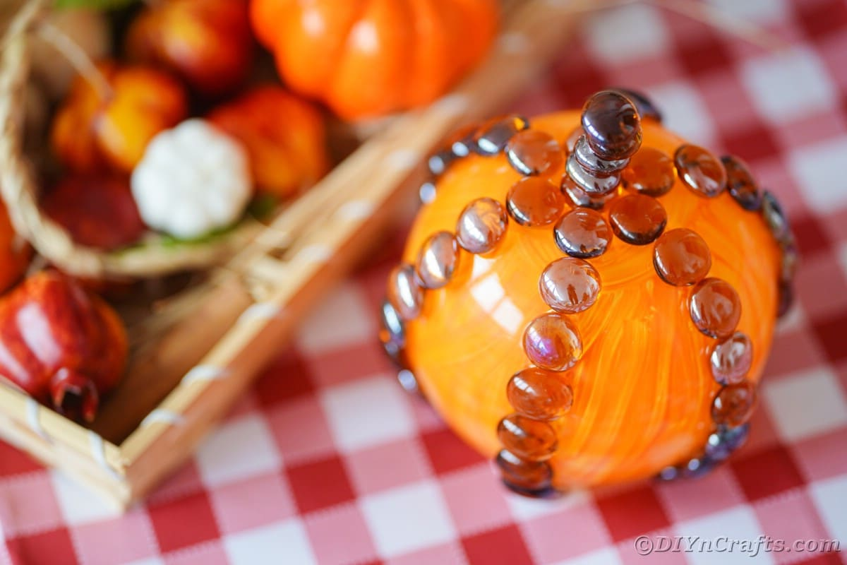 Wooden tray of fake fall items next to fake glass pumpkin
