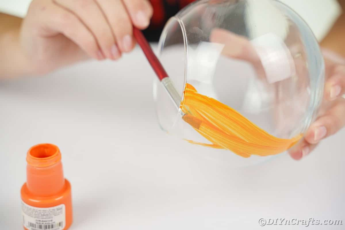 Hand painting the inside of a glass bowl orange