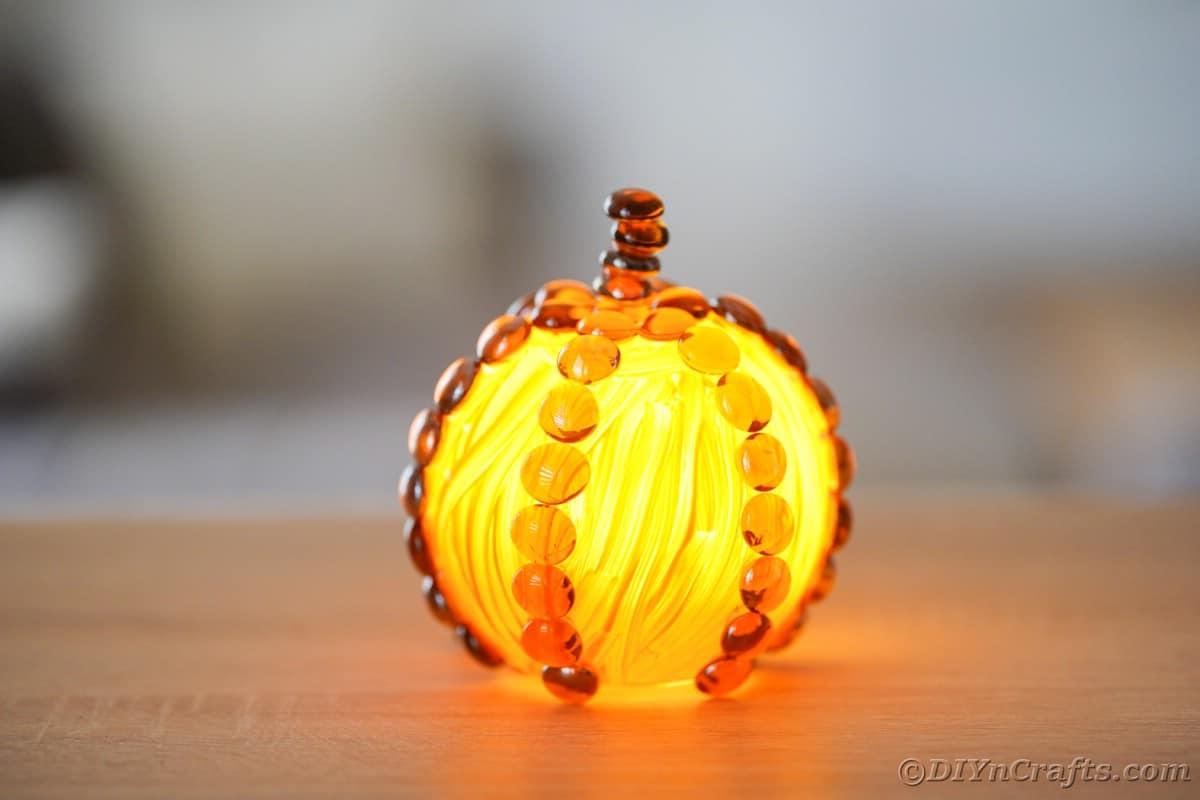 Glass lantern shaped like pumpkin on table