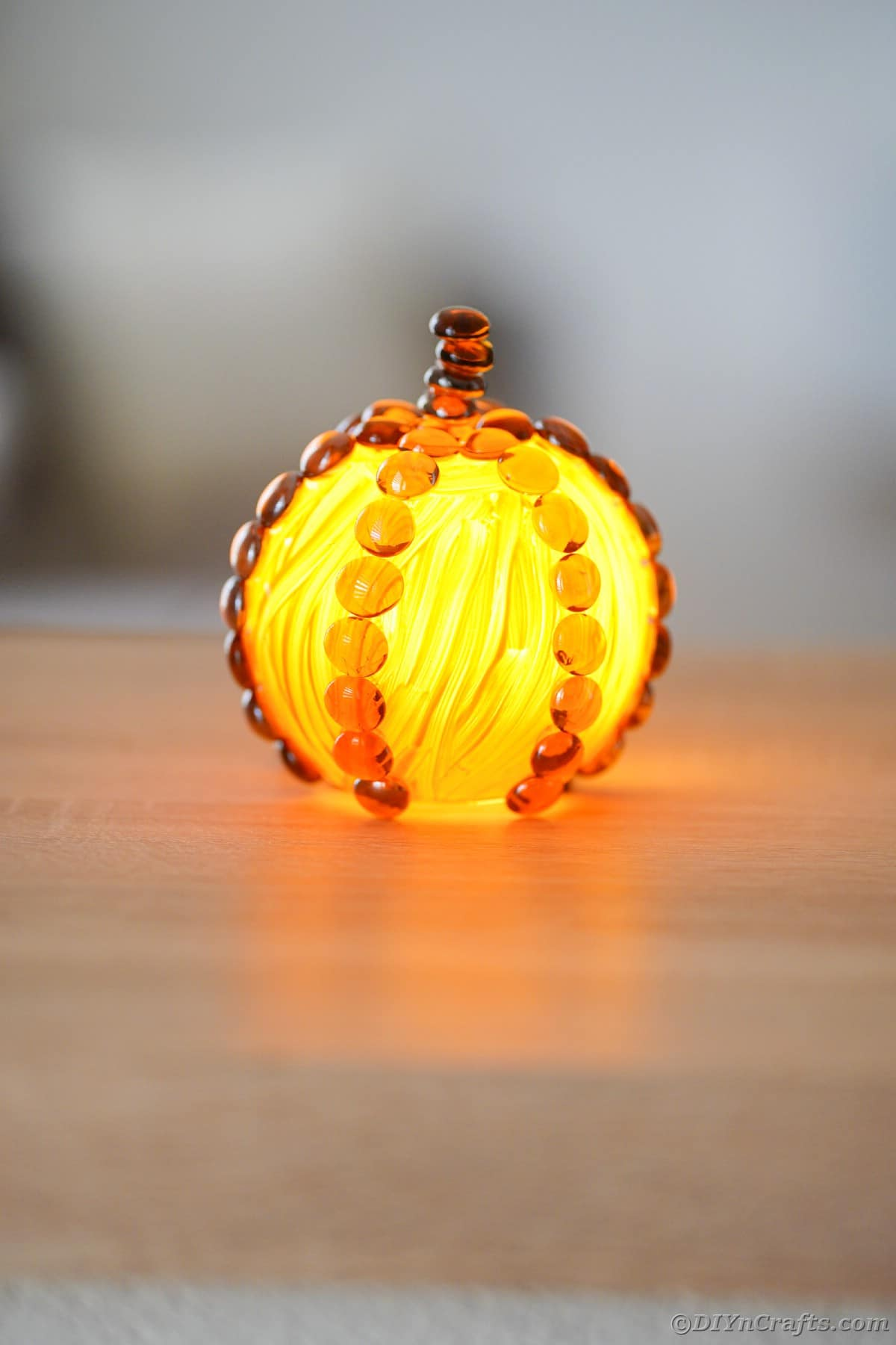 Painted glass pumpkin on table with candle inside
