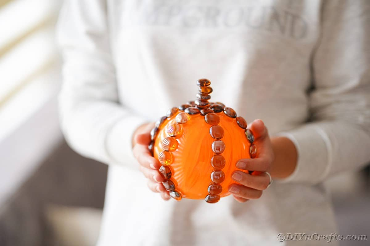 Woman in white holding glass pumpkin