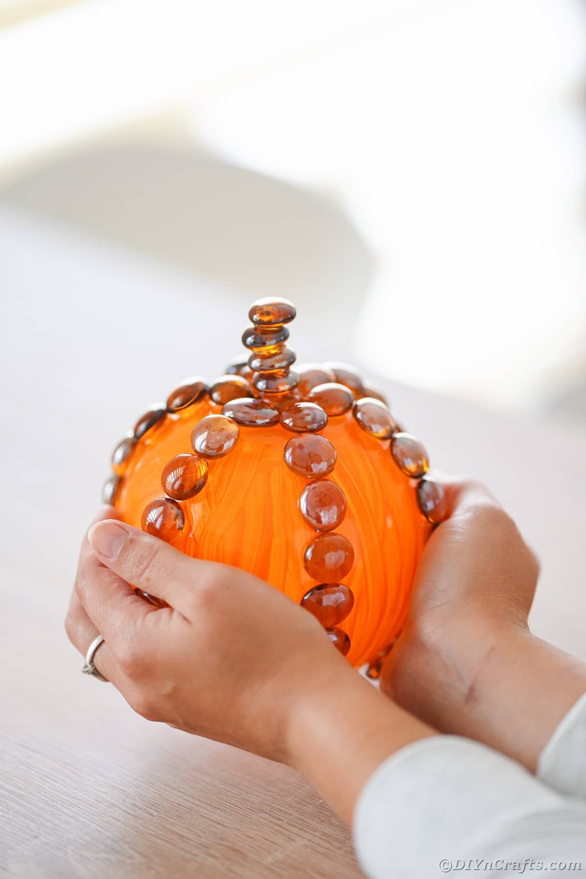 Hands holding glass pumpkin on table