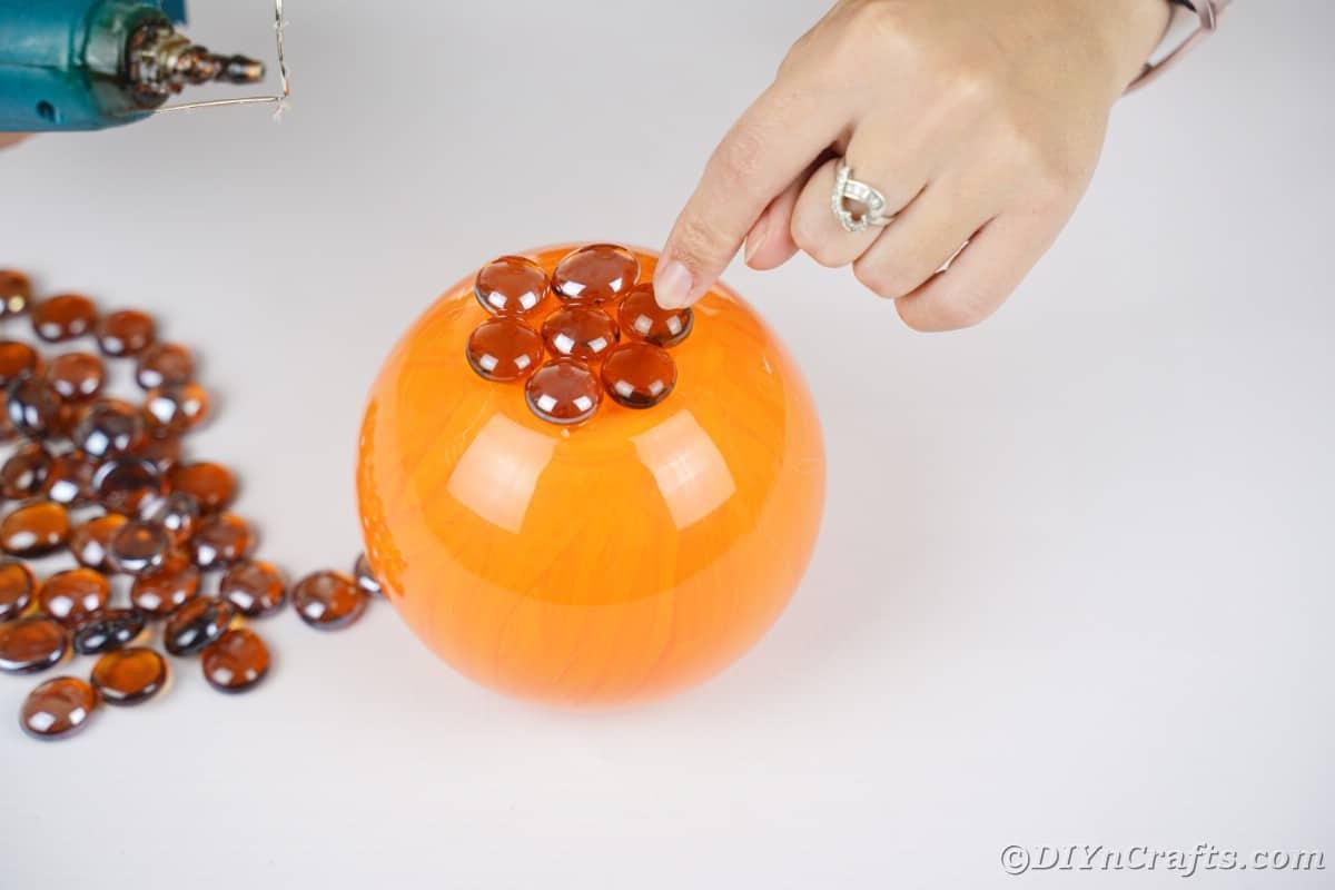 Hand gluing brown rocks on top of orange bowl