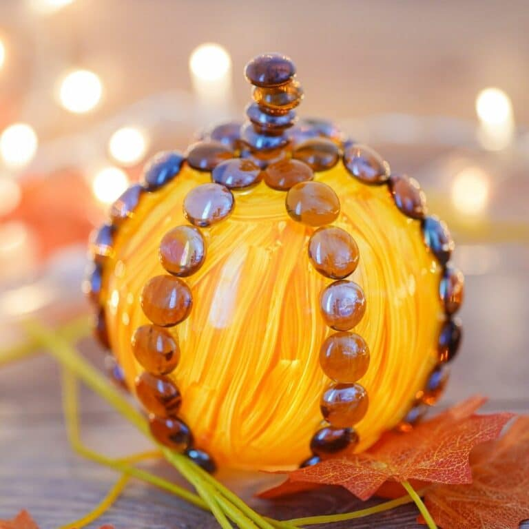 Fake pumpkin on table with twinkle lights in background