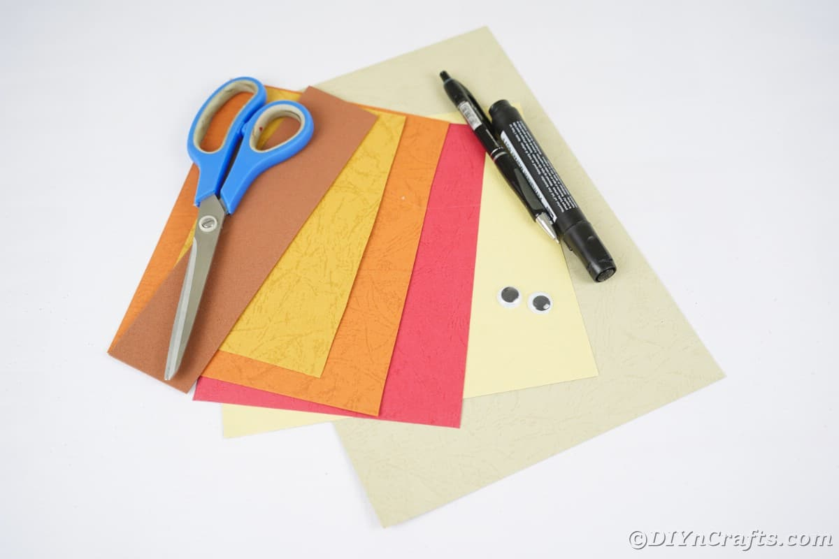 Craft paper in fall colors on white table with scissors and pens on top of them