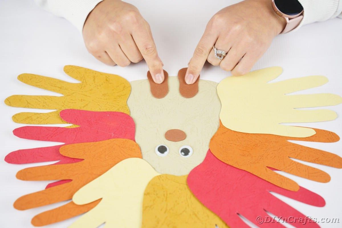 Fingers holding foam feet on bottom of paper hedgehog