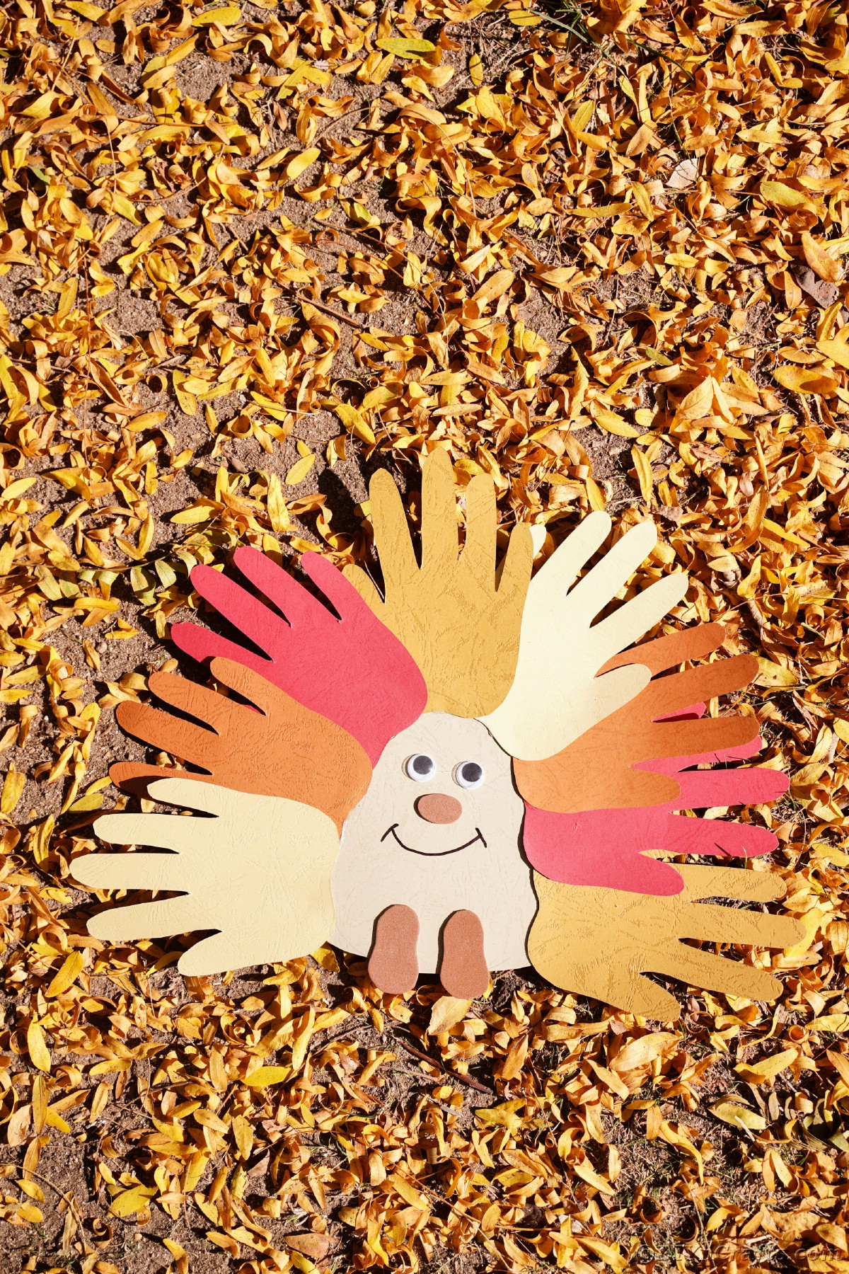 Fallen yellow leaves on ground topped with handprint paper hedgehog