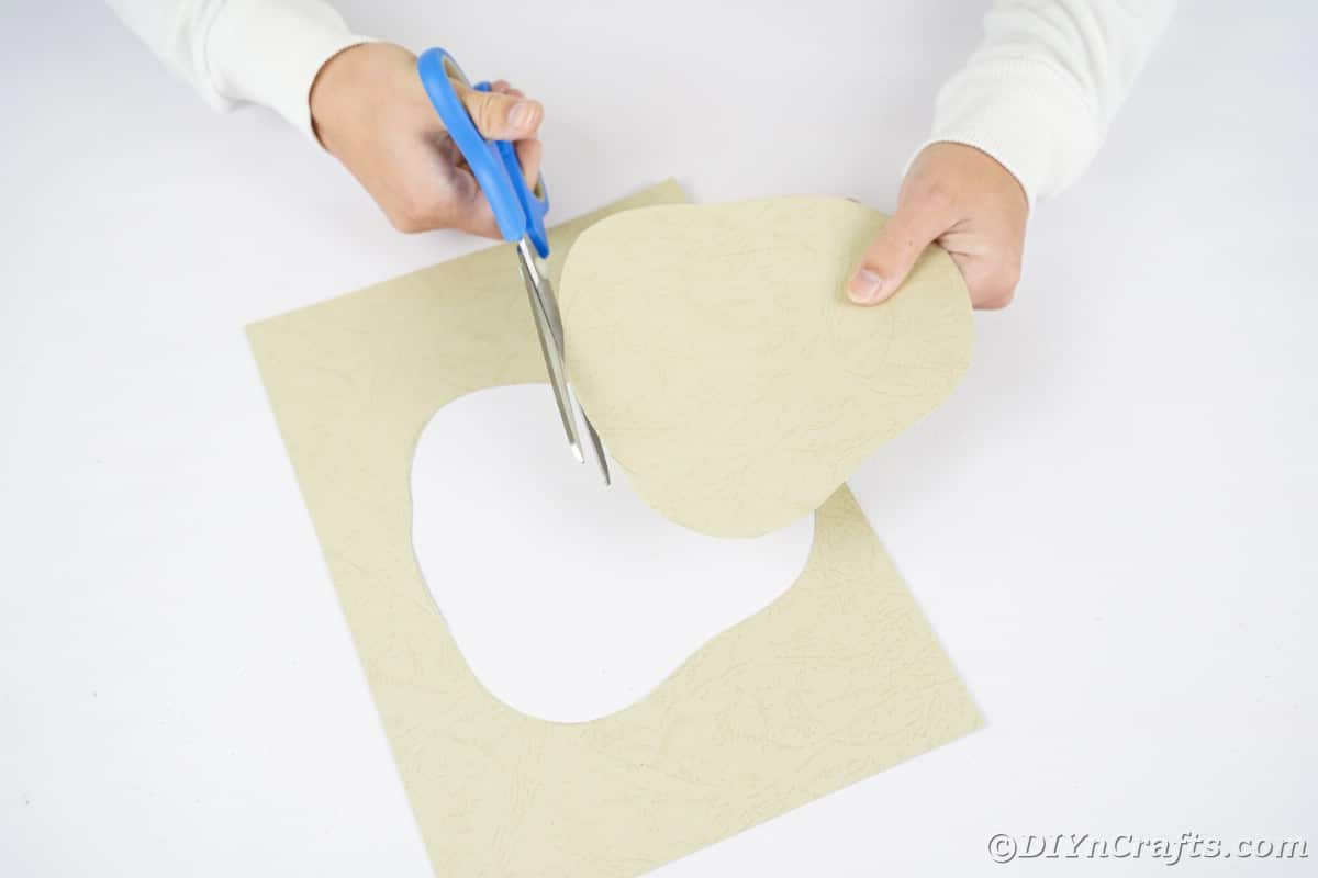 Blue scissor in hand cutting shape out of tan paper