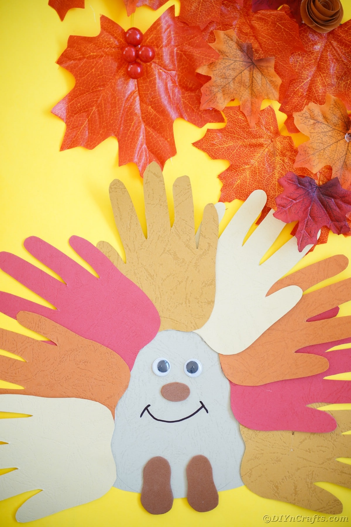 Yellow background with fake leaves and a handprint hedgehog craft on top