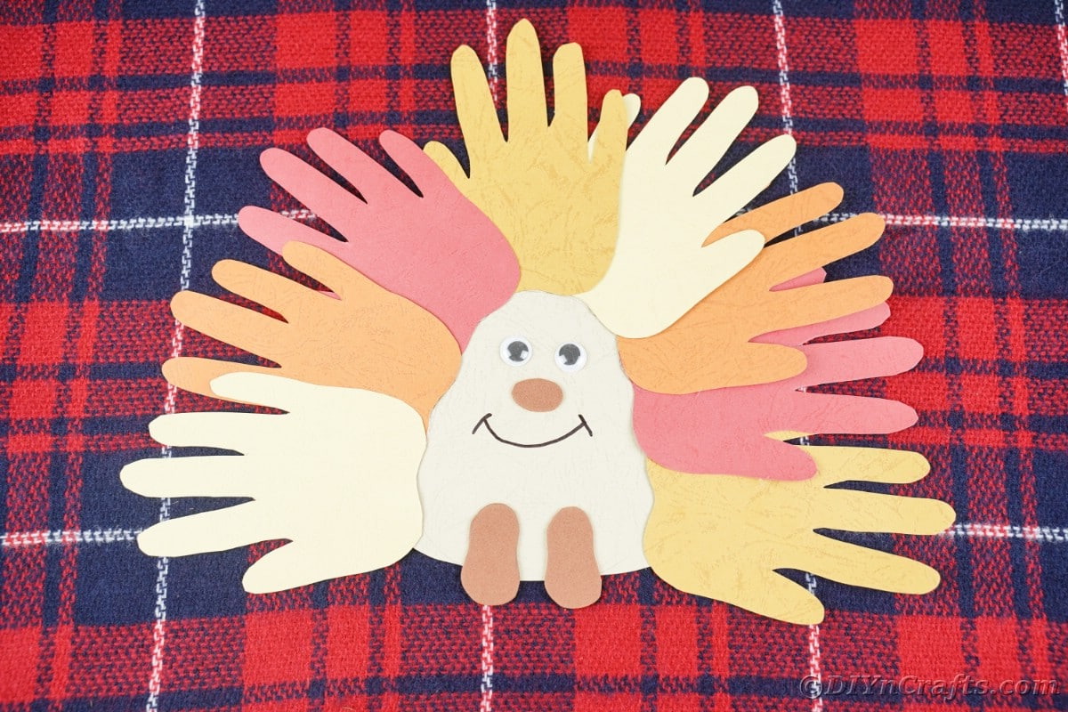 Handprint hedgehog in fall colors laying on plaid fabric