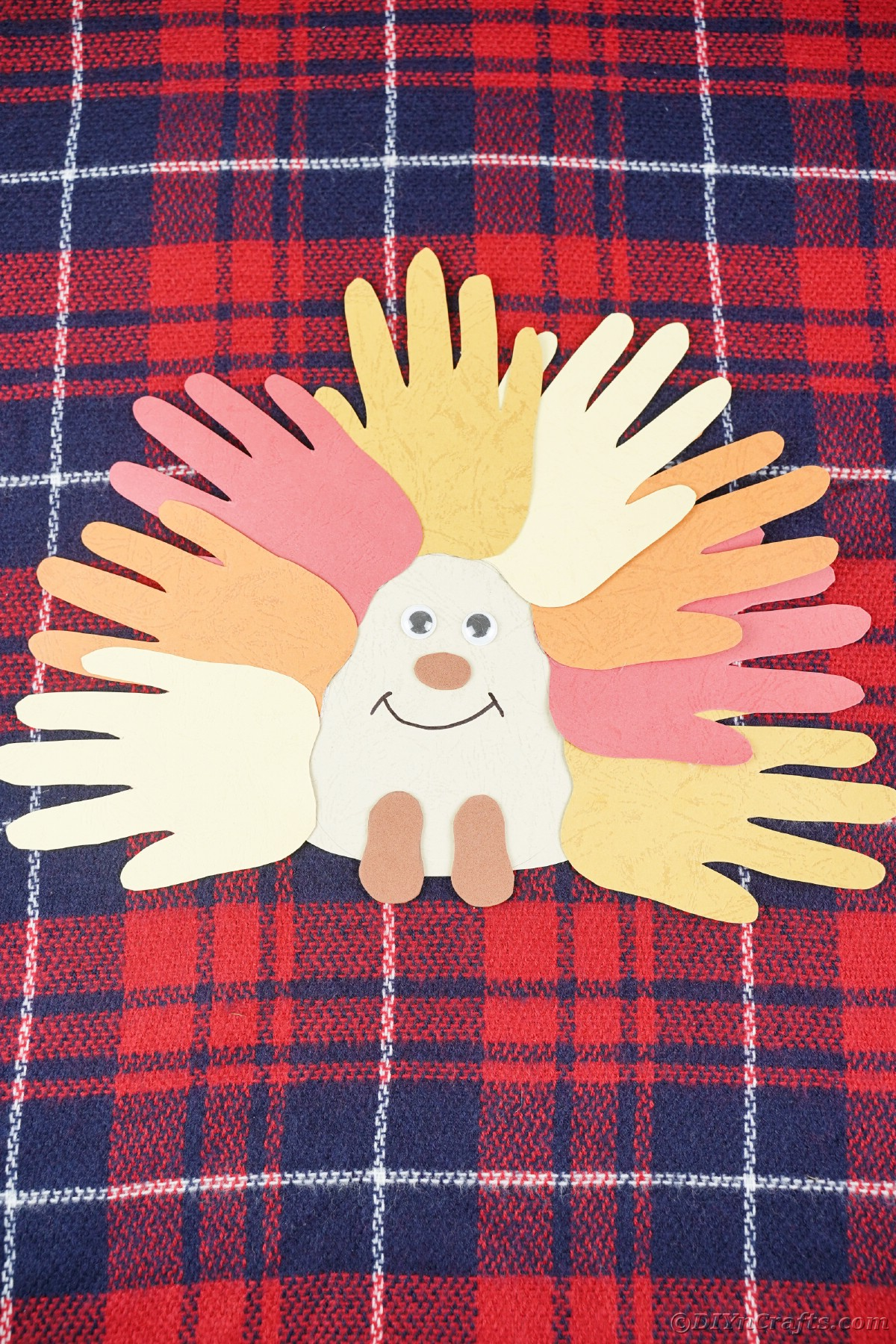 Blue and red plaid fabric on surface with paper hedgehog on top