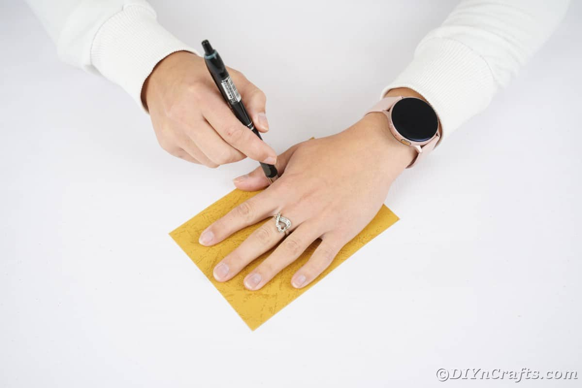 Hand being traced onto oraneg paper
