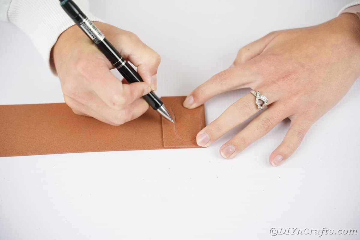Hand holding pin over brown foam paper