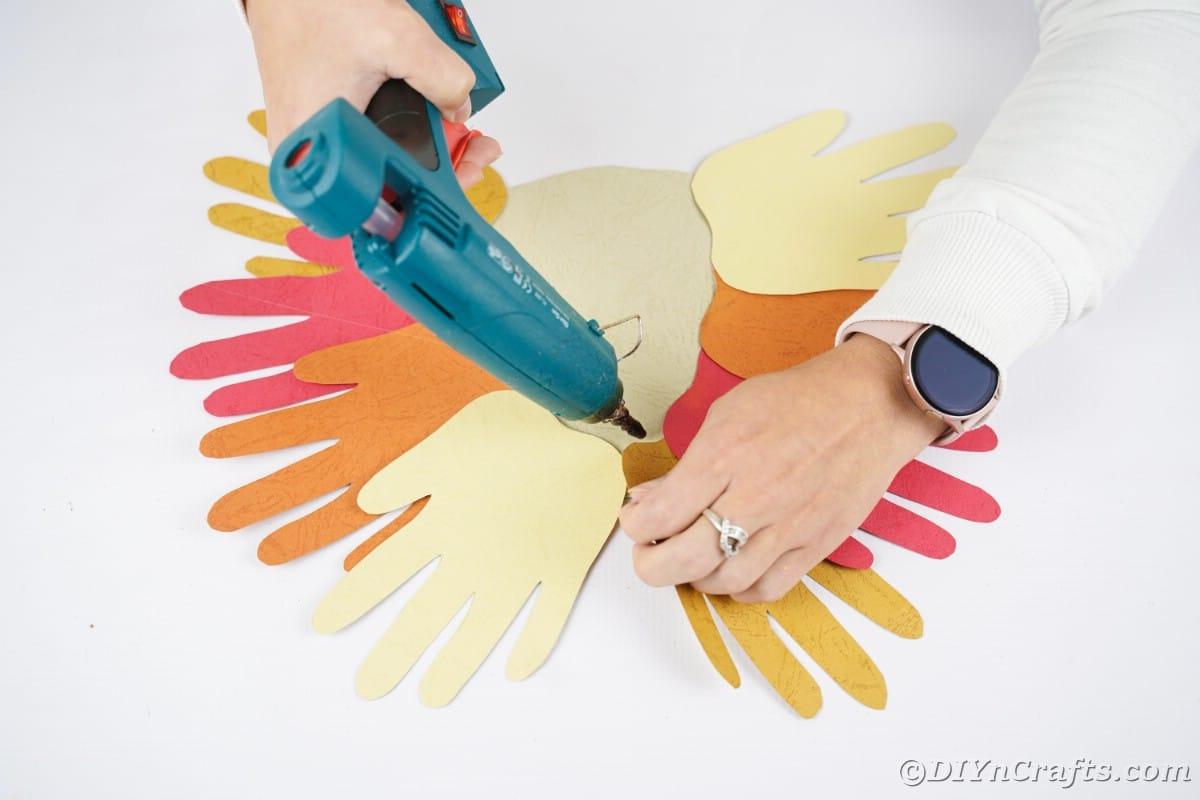 Hand holding blue hot glue gun above paper handprints