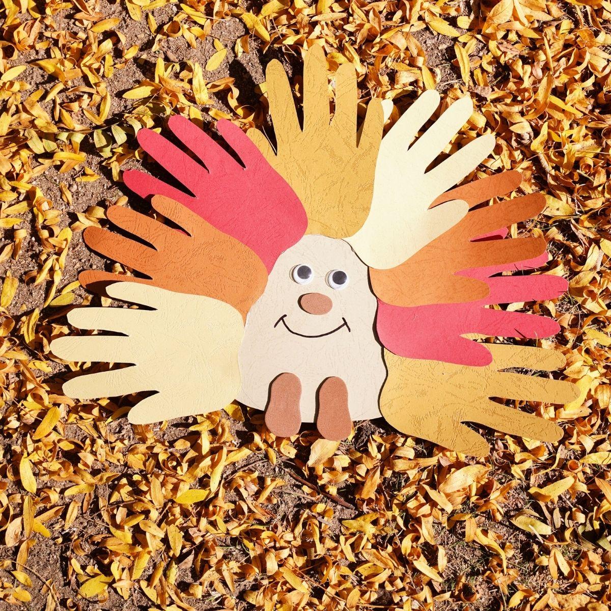 Handprint hedgehog laying on fallen leaves