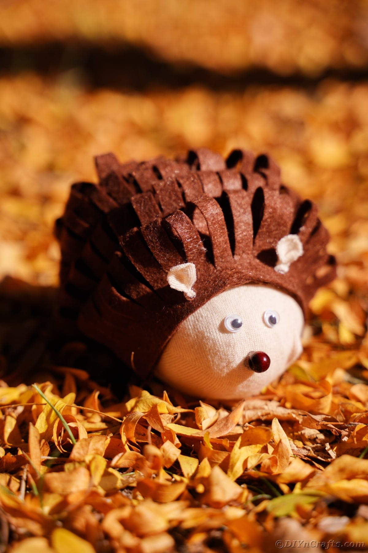 Brown and tan fabric hedgehog on yellow leaves