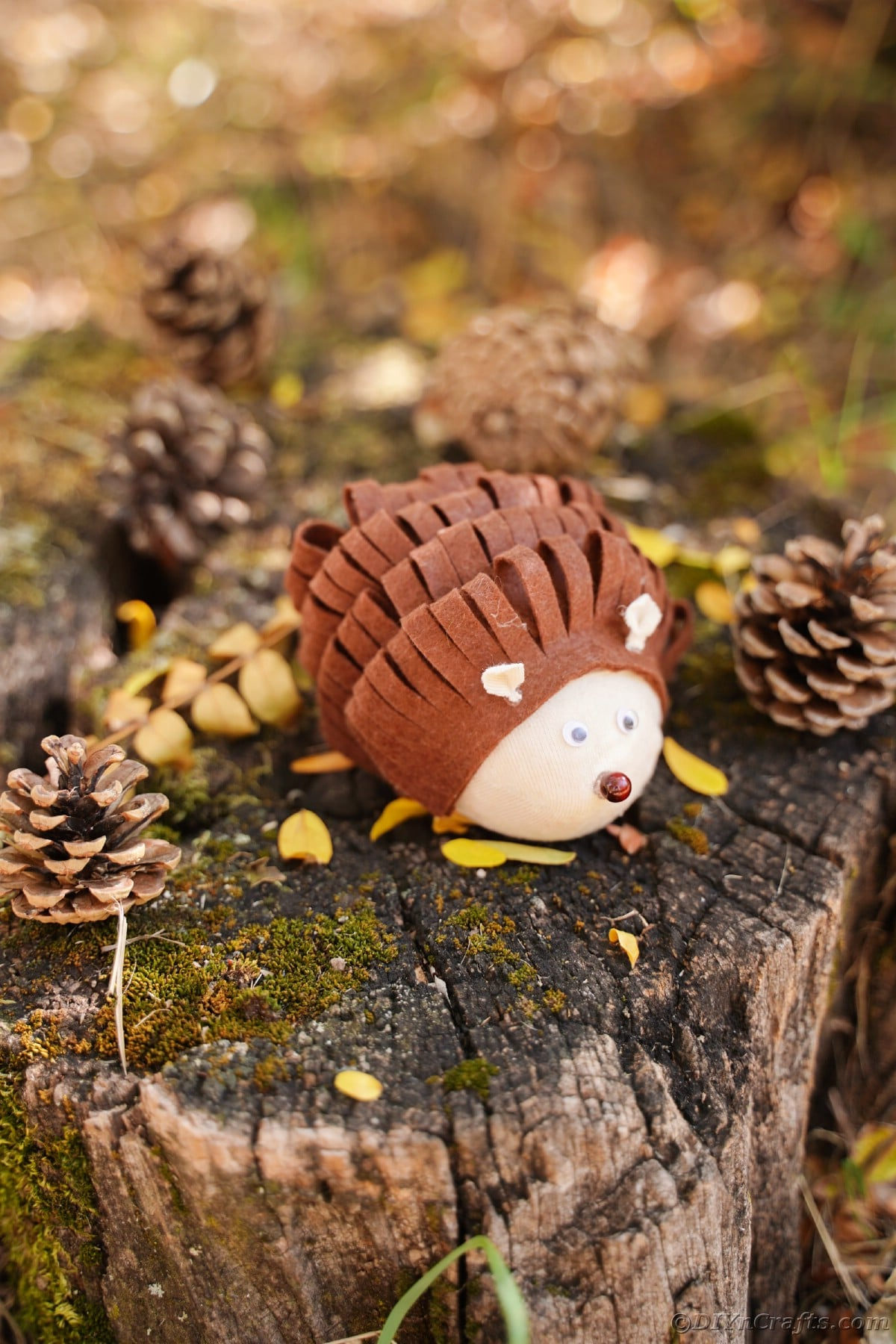 Brown and tan toy critter on stump by pinecones