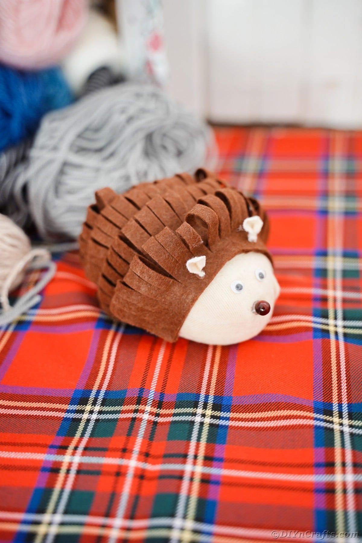 Stuffed toy hedgehog on red plaid blanket by rolls of yarn