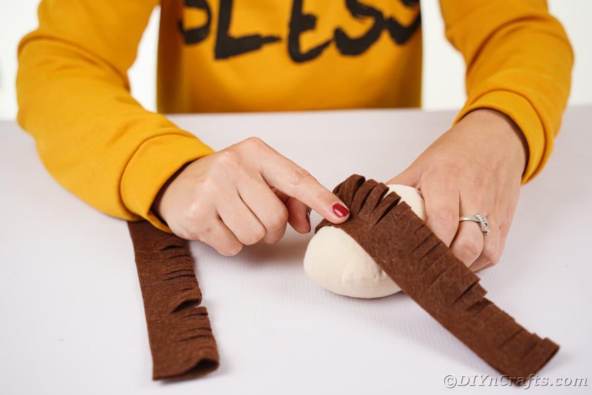Hands gluing fringed felt onto stuffed sock